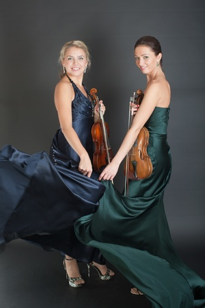 portrait of two violinists on a black background photo