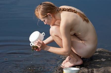 camp life - girl washes dishes in the lake Stock Photo - 16011716