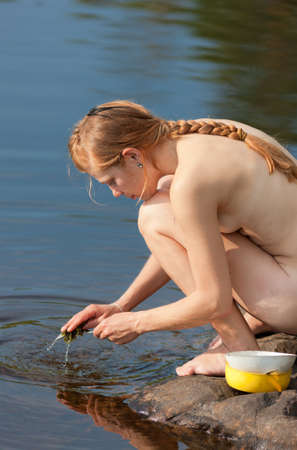 camp life - girl washes dishes in the lake photo