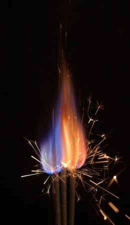 pyrotechnic burning fire and sparks closeup on black background photo