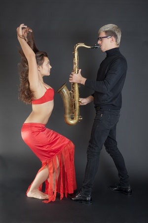 man playing the saxophone for a girl dancer photo