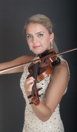 portrait of a girl violinist on dark background photo