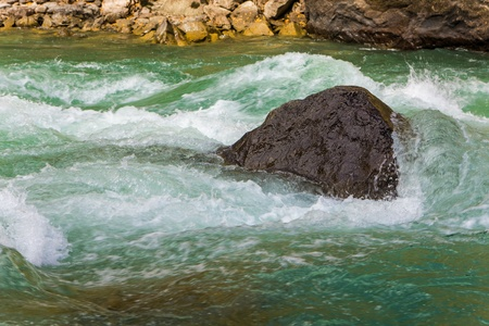 stone in the water fast mountain river photo