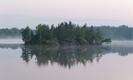 island on the lake in the woods with the morning mist photo