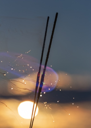sparklers with color flames on the background of the sunset sky photo