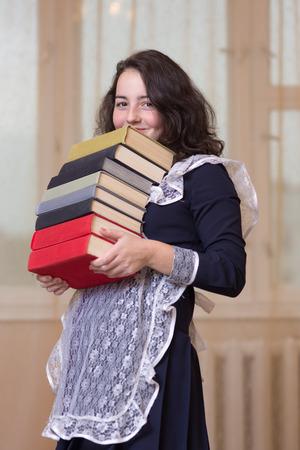 colegiala: colegiala con una pila de libros pesados