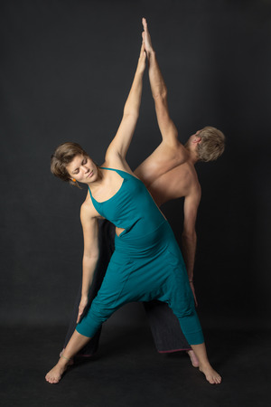 trikonasana: couple in yoga pose Trikonasana on black  Stock Photo