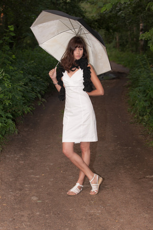 girl in white dress with umbrella on a forest road photo
