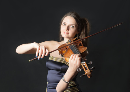 portrait of a girl violinist on black background photo