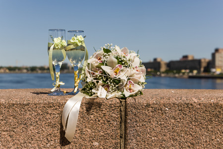 wedding accessories - bridal bouquet and glasses on the parapet photo