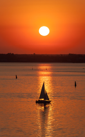 Sailing vessel silhouette in the sea at sunset photo
