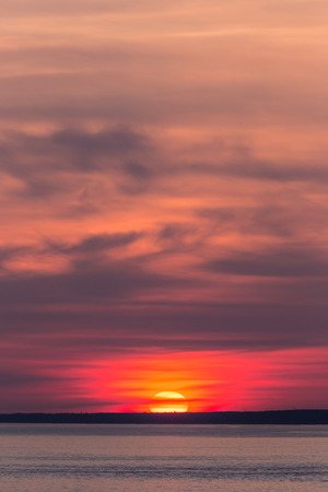 bright setting sun in the clouds on the horizon photo
