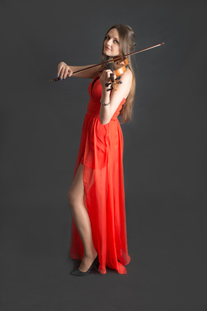 portrait of a girl violinist in red dress photo