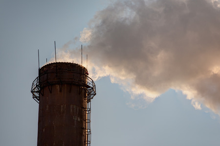 tall chimney: Smoke from high pipes against the sky