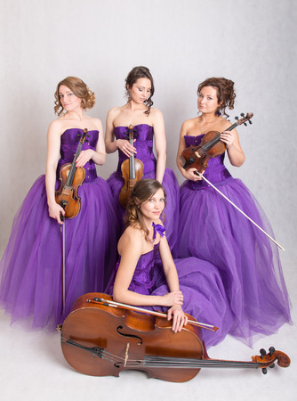 the quartet: musical quartet in evening dresses with strings Stock Photo