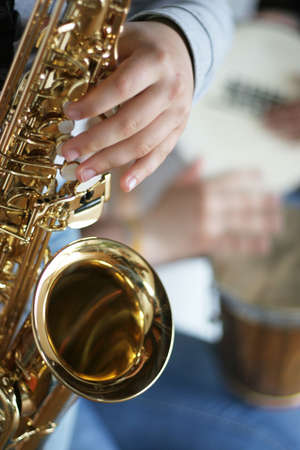 saxophone: Saxophone player with drums in the background - focus on the finger of the saxophone player Stock Photo