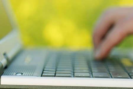 hands free: Borrosa lado trabajando en una computadora port�til con flores de color amarillo en el fondo. (La atenci�n se centra en el primer plano en el borde de la computadora port�til)