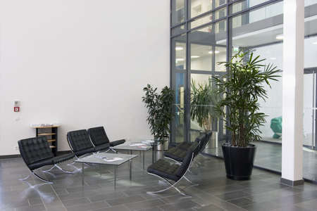 Lobby of a modern office building with chairs of black leather, tables of glass and plants Stock Photo