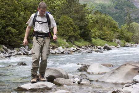 Man with backpack crossing a river in the mountains Stock Photo - 1063942