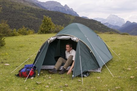 Mountaineer in his tent on a meadow with mountains in the background Stock Photo - 1063943