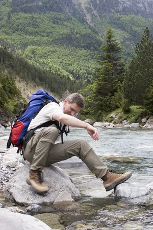 Man with backpack resting on a stone in a mountain river Stock Photo - 1063946