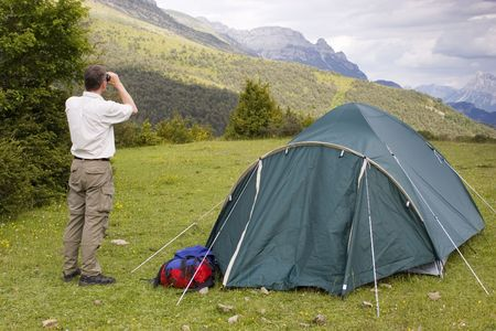 Mountaineer beside his tent looking with binoculars at the bad weather. Stock Photo - 1068004