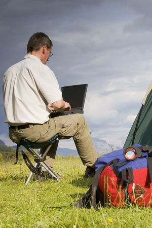 Man working with laptop beside his tent in the mountains Stock Photo