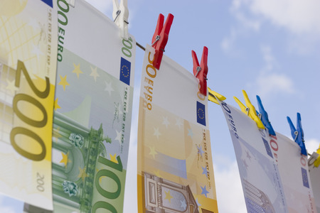 European banknotes on a clothesline against cloudy sky photo