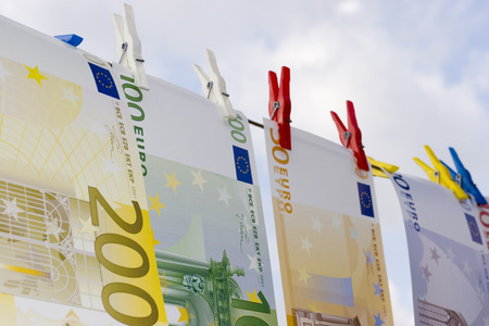Euro banknotes on a clothesline against cloudy sky photo