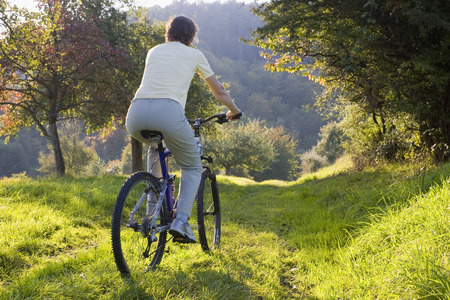 mountainbike: Woman on a mountainbike at sunset in autumn