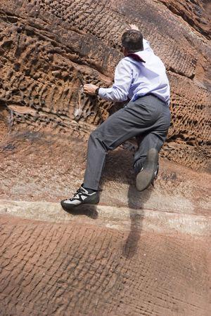 escalando: Empresario Cravat escalada con una roca  Foto de archivo