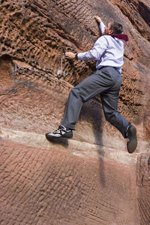 Businessman with cravat climbing a rock Stock Photo