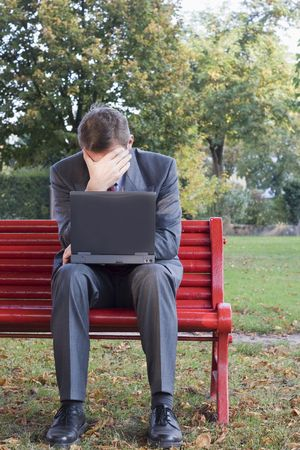 overwrought: Tired businessman with laptop sitting on a park bench