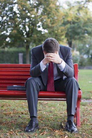 banc parc: Inquiet homme d'affaires assis sur un banc de parc rouge