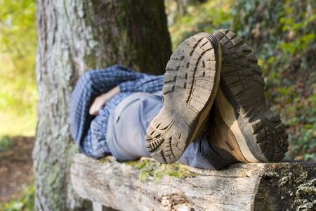 Hiker lying on a wooden bench. Focus on the boots in the foreground. Stock Photo
