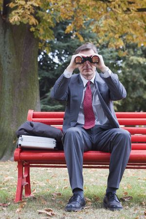 Businessman on a red park bench searching with binoculars Stock Photo - 1932089