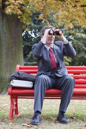 Businessman on a red park bench looking through binoculars Stock Photo - 2020003