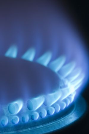 consume: Blue flames of a gas stove in the dark