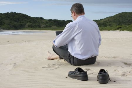 Businessman working with his laptop while sitting barefoot on the beach. photo