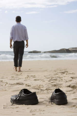 relaxed man: Manager walking barefoot on the beach. Focus on the shoes in the foreground Stock Photo