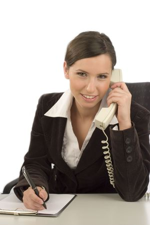 Young smiling businesswoman with telephone taking notes photo