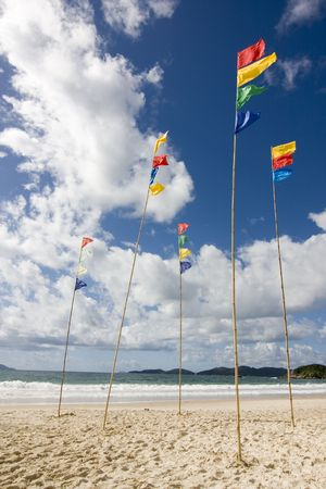 flagpoles: Flagpoles with colorful flags on the beach against blue sky with white clouds