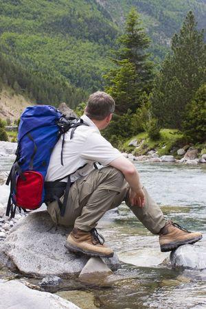 perdido: Hiker with backpack resting at a mountain creek. National park Ordesa y Monte perdido - Spain