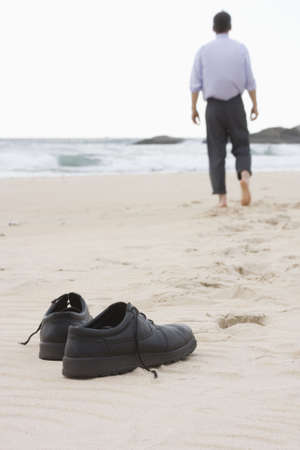 Businessman walking barefoot on a beach. Focus on his shoes in the foreground. Stock Photo