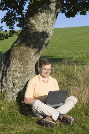 Man typing on a laptop while sitting in a meadow Stock Photo - 3008782