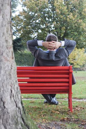 Businessman relaxing on a red park bench photo