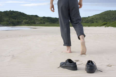 Businessman walking barefoot on a empty beach. Focus on his shoes in the foreground
