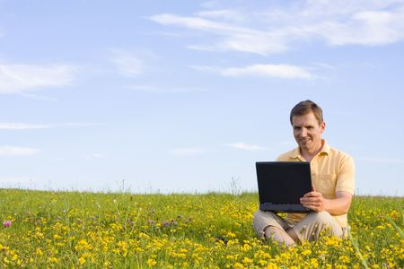 Smiling man sitting with laptop computer in a meadow with yellow flowers