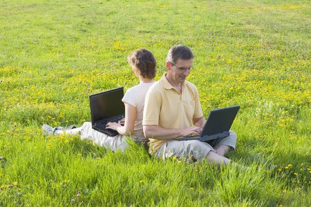 Couple sitting in meadow while working with laptops photo