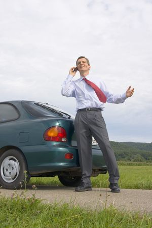 Smiling businessman talking on mobile phone beside his car Stock Photo - 3413660
